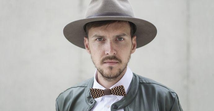 Hnědý pánský klobouk Apis Hat na modelu v kožené bundě s dřevěným motýlkem Decorum