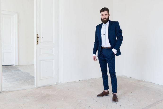 Muž v modrém obleku s bílou košilí a sponou na kravatu