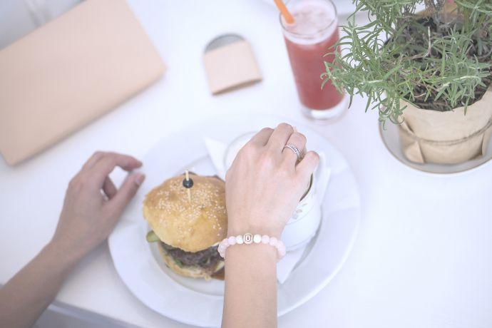 Oběd v restauraci na stole leží kožené dámské psaníčko Lux Clutch a dřevěné zrcatko Liti