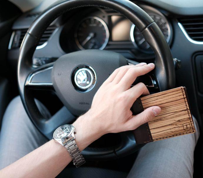 Muž za volantem s dřevěnou peněženkou Nox Virilia
