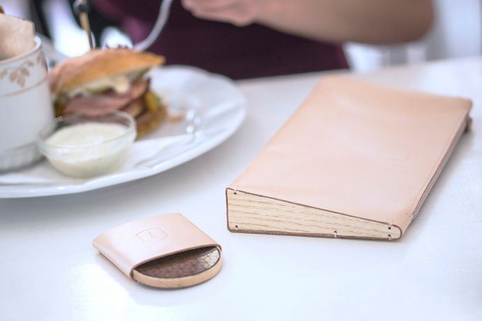 Dřevěné kožené psaníčko Lux Clutch a dřevěné zrcátko Liti položené v restauraci na stole