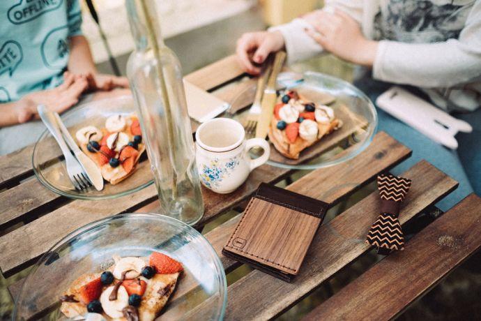 Na stole v restauraci položená dřevěná peněženka Nox Virilia a dřevěný motýlek Trio