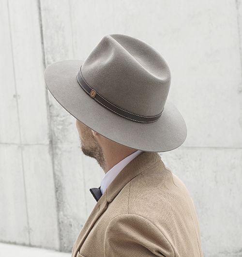 Muž v béžovém saku s elegantním kloboukem Apis hat a dřevěným motýlkem na krku