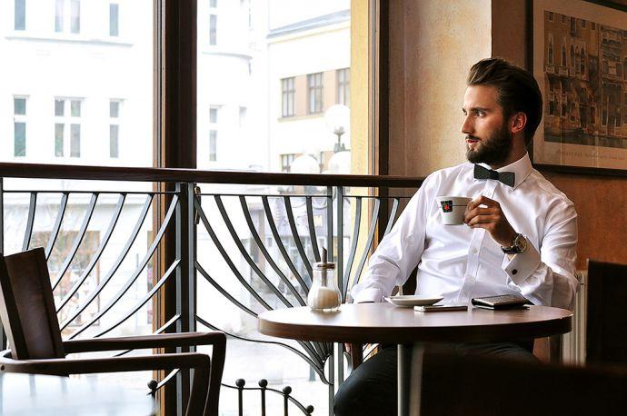 Muž popíjející kávu v bílé košili s černým dřevěným motýlkem Taurum