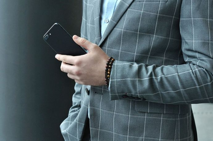 Muž v šedém saku s mobilem v ruce na které má originální BeWooden náramky