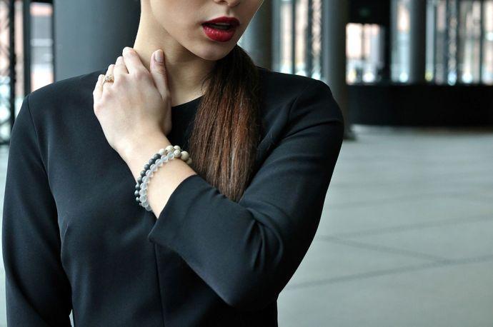 Žena v černých šatech na rukou má unikátní náramky s dřevěným detailem