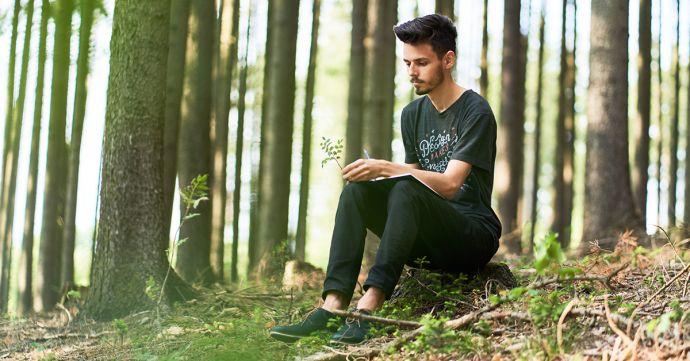 Muž sedí v lese a píše do BeWooden zápisníku