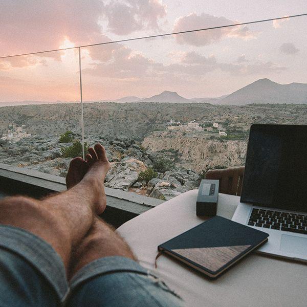 Muž sedí u okna a vedle sebe má zápisník Ocean Notebook