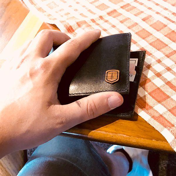 Muž držící koženou peněženku v ruce