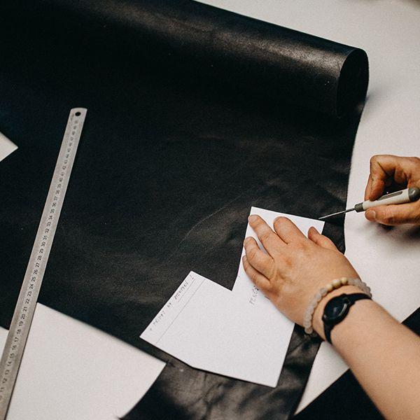 Žena vyřezává kožené části na výrobu peněženky