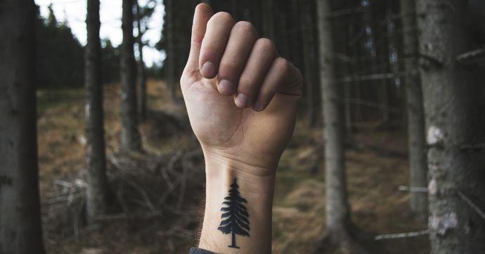 Muž v lese s vytetovaným stromem na ruce