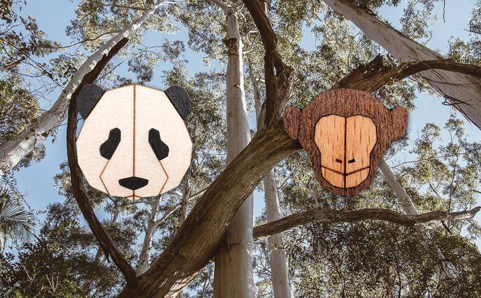 Dřevěné brože opice a panda na obrázku tropické přírody