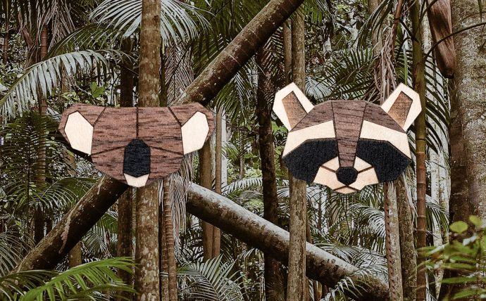 Dřevěné brože koala a mýval na obrázku tropické přírody
