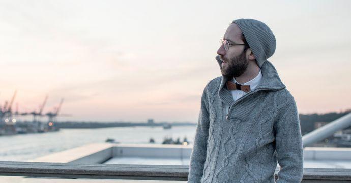 Muž stojící venku v šedém svetru a čepici ma na krku dreveneho motylka