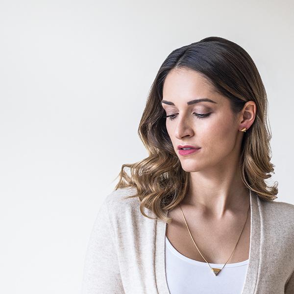 Drobná brunetka v béžovém svetříku se zlatým náhrdelníkem Liti Necklace Triangle