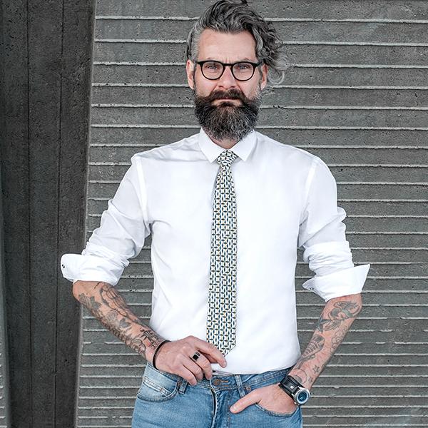 Muž středního věku s potetovanýma pažema a kravatou Meria Tie