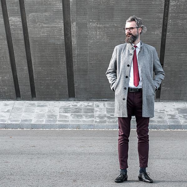 Elegantní starší muž v šedém kabátě s červenou kravatou Wine Tie