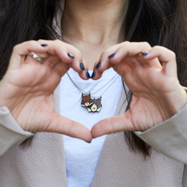 Žena má prsty sevřené do tvaru srdíčka, ve kterém jsou Squirrel Pendant a Lynx Pendant