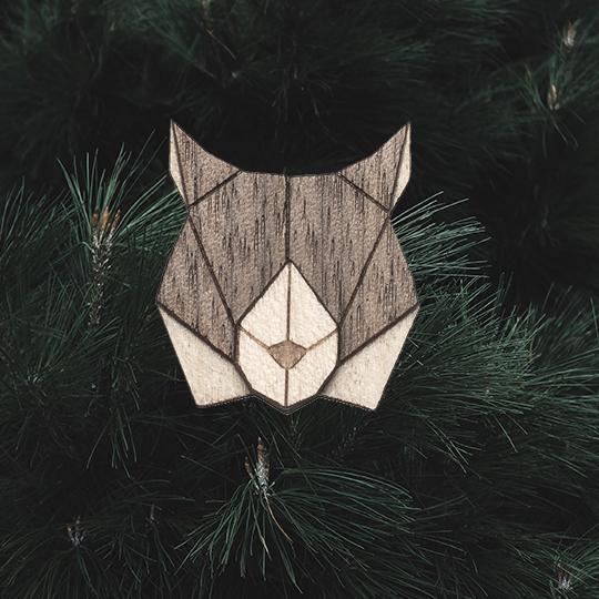 Detail dřevěné brože Lynx Brooch na lesním pozadí