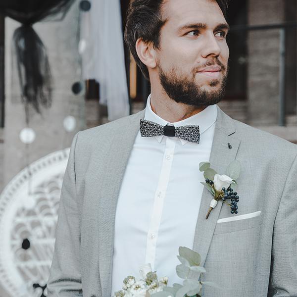 Vousatý ženich v šedém saku a s dřevěným motýlkem Cassio čeká na svou nevěstu