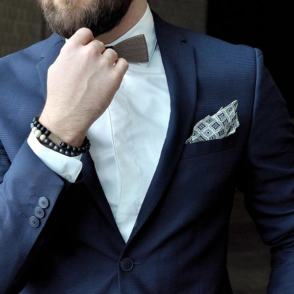 Elegantní muž v modrém saku s luxusními korálkovými náramky BeWooden