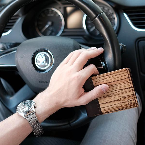Muž v autě s dřevěnou peněženkou Lineari s koženými detaily