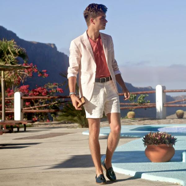 Elegantní mladý muž u bazénu držící dřevěnou peněženku