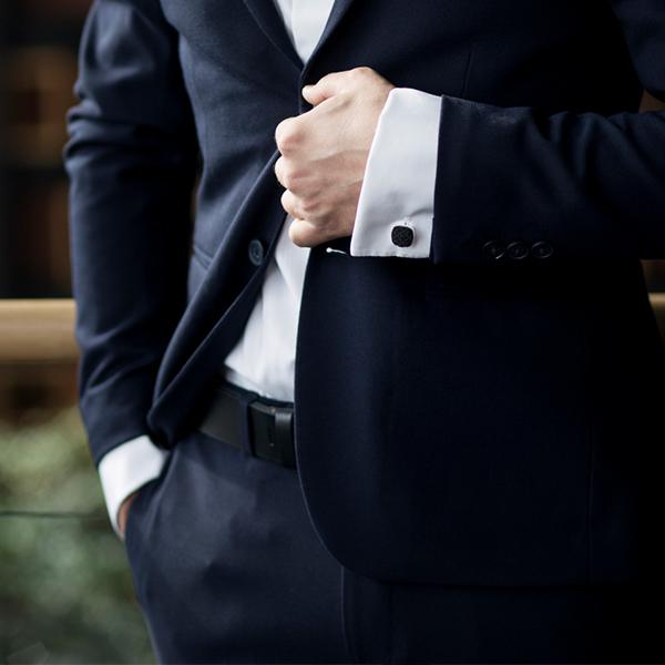 Muž v tmavě modrém obleku s černým koženým opaskem Taurum Belt a stříbrnými manžetovými knoflíčky
