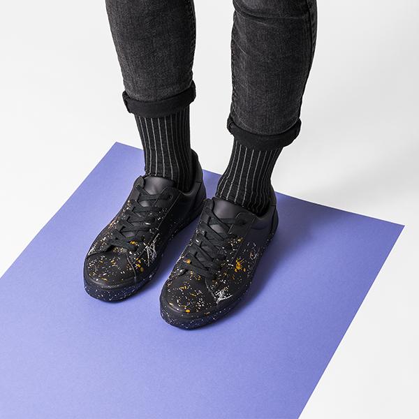 Muž ve strakatých teniskách s černo-šedě pruhovanýma ponožkama Nox Socks