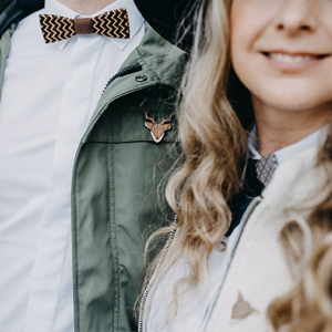 Woman and man with bow ties and brooches