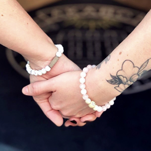Two hands decorated with pearl bracelets